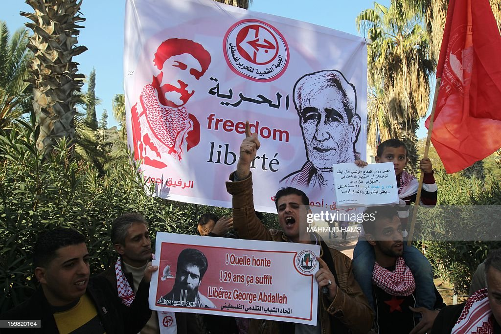 Palestinian supporters of the Popular Front for the Liberation of Palestine (PFLP) take part in a protest outside the French Cultural Center calling for the release of Lebanese militant Georges Ibrahim Abdallah (portrait L) and Ahmed Saadat, leader PFLP (portrait R), in Gaza City on January 21, 2013. AFP PHOTO/MAHMUD HAMS