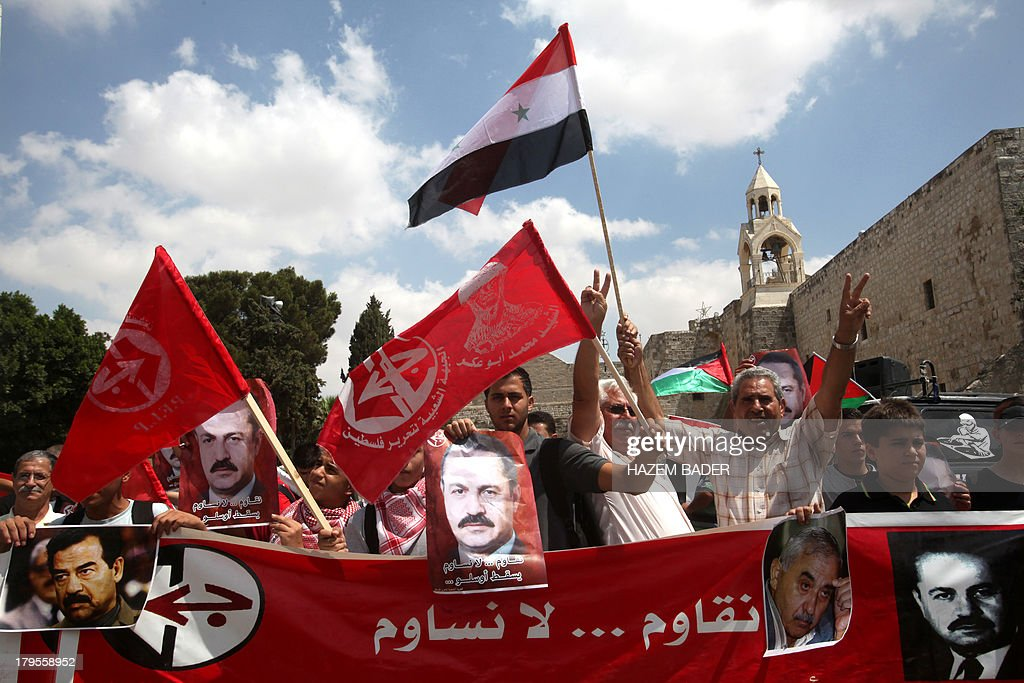 Palestinian supporters of the Popular Front for the Liberation of Palestine (PFLP) wave their party's flag and pictures of its founder George Habash, during a protest near the Nativity Church in the West Bank town of Bethlehem on September 5, 2013, against US military intervention in Syria. President Barack Obama's plan to conduct military strikes on Syria passed its first congressional hurdle on September 3, 2013, paving the way for a full Senate debate on the use of force.