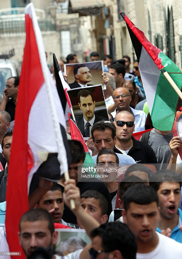 Palestinian supporters of the Popular Front for the Liberation of Palestine (PFLP) wave the Syrian flag (front) during a protest near the Nativity Church in the West Bank town of Bethlehem on September 5, 2013, against US military intervention in Syria. President Barack Obama's plan to conduct military strikes on Syria passed its first congressional hurdle on September 3, 2013, paving the way for a full Senate debate on the use of force. AFP PHOTO/HAZEM BADER