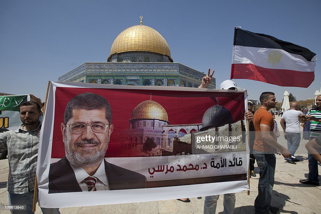 Palestinian supporters of the radical Islamist movement Hamas hold a poster of Egypt's ousted president Mohamed Morsi and Egypt's national flag as they rally in support of the former Islamist leader and against the crackdown on protest camps in Cairo, outside al-Aqsa mosque compound in Jerusalem on August 16, 2013. Egypt's Islamists called for a 'Friday of anger' after nearly 600 people were killed as security forces cleared their protest camps in the Egyptian capital.