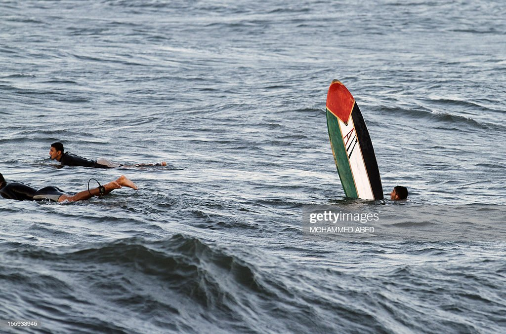 A Palestinian surfer as he swims with his surf board off the coast of the Gaza Strip in the Mediterranean Sea on November 9, 2012. Life in the poor and crowded Gaza Strip is going to get harsher still unless action is taken now, according to a new United Nations report.