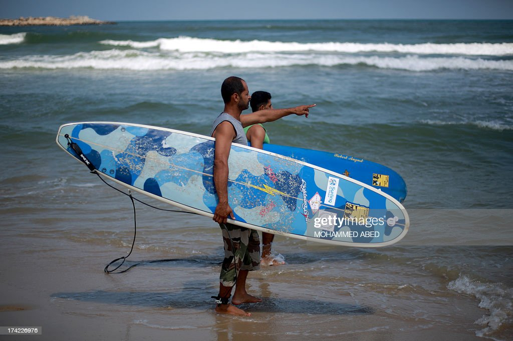 Palestinian surfers Ahmed Abo-Hasera and Mohammed Abo-Jyab hold their surfboards talking before going surfing at Gaza City beach on July 22, 2013. AFP PHOTO/MOHAMMED ABED