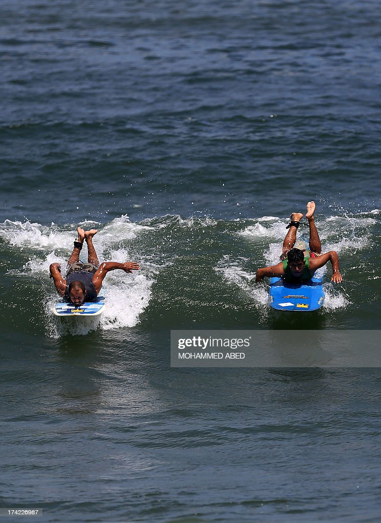 Palestinian surfers Ahmed Abo-Hasera (R) and Mohammed Abo-Jyab surf at Gaza City beach on July 22, 2013. AFP PHOTO/MOHAMMED ABED