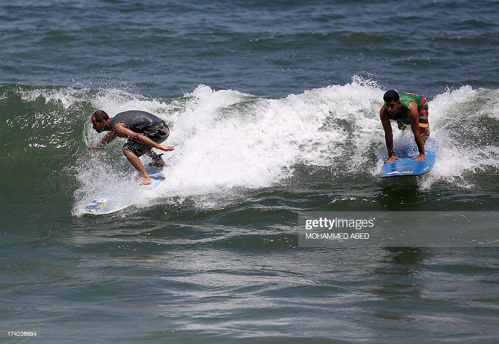 Palestinian surfers Ahmed Abo-Hasera (R) and Mohammed Abo-Jyab surf at Gaza City beach on July 22, 2013.
