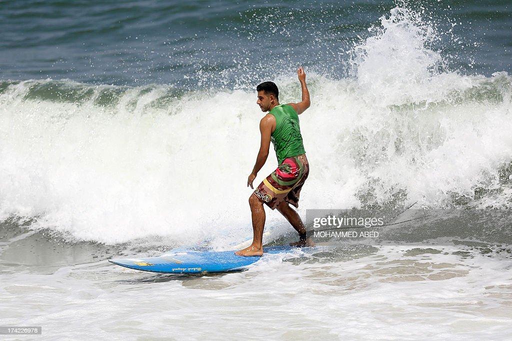 Palestinian surfers Ahmed Abo-Hasera surfs at Gaza City beach on July 22, 2013.