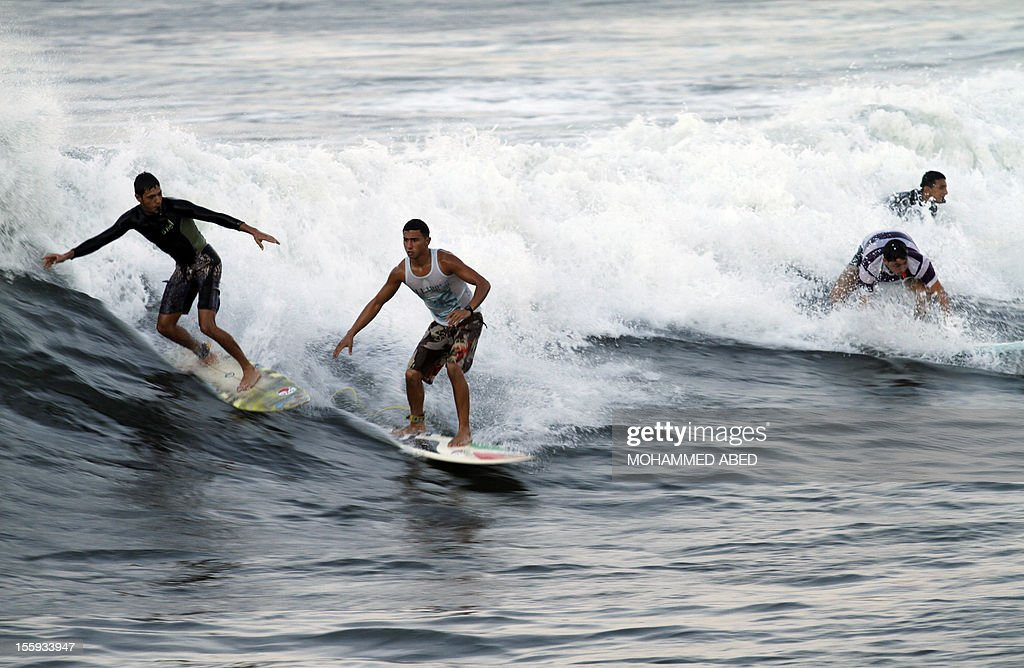 Palestinian surfers ride a wave off the coast of the Gaza Strip in the Mediterranean Sea on November 9, 2012. Life in the poor and crowded Gaza Strip is going to get harsher still unless action is taken now, according to a new United Nations report.