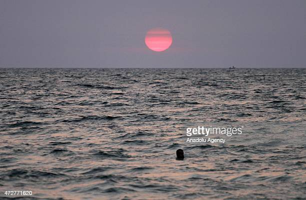 Palestinian swims in the sea at the Gaza shore at sunset in Gaza City Gaza on May 9 2015