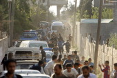 Palestinian take cover during clashes between Hamas security forces and the alleged killers of Italian activist Vittorio Arrigoni in the Nusseirat...
