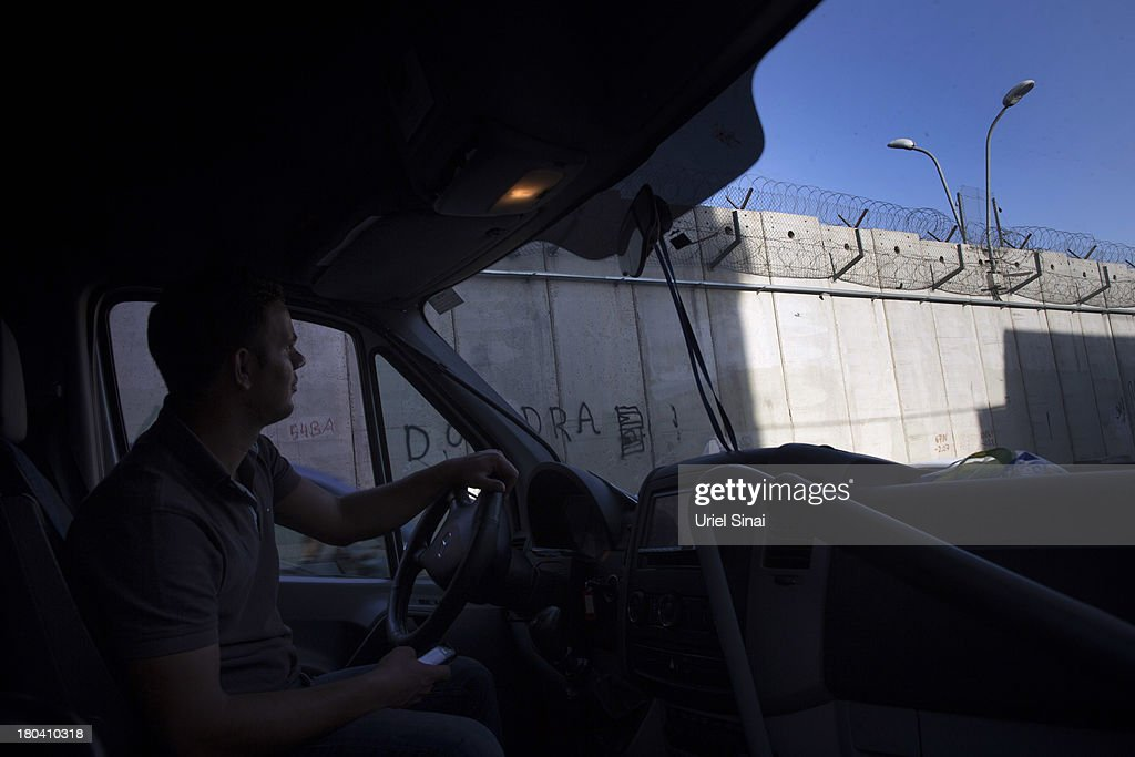 A Palestinian taxi driver waits for costumers along the Israeli West Bank barrier on the outskirts of Jerusalem on September 12, 2013 in Aram, West Bank. The twenty-year anniversary of the Oslo Accord, which was to set up a framework for peace between Israel and Palestine, will be marked on September 13.