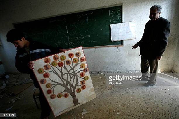 Palestinian teacher and a student inspect a damaged classroom in the destroyed AlAqsa university building at the crossing of the Israeli Jewish...