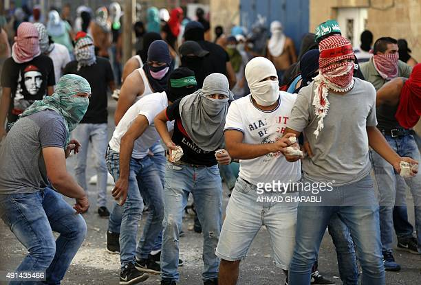 Palestinian throw stones are seen on the streets during clashes with Israeli security forces in the Palestinian neighborhood of Shuafat in east...