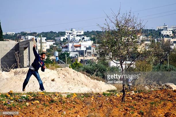 Palestinian throwing rock in Bil'in, West Bank