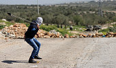 A Palestinian throws a stone against Israeli security forces during clashes following a protest against closure of the village road in the West Bank...