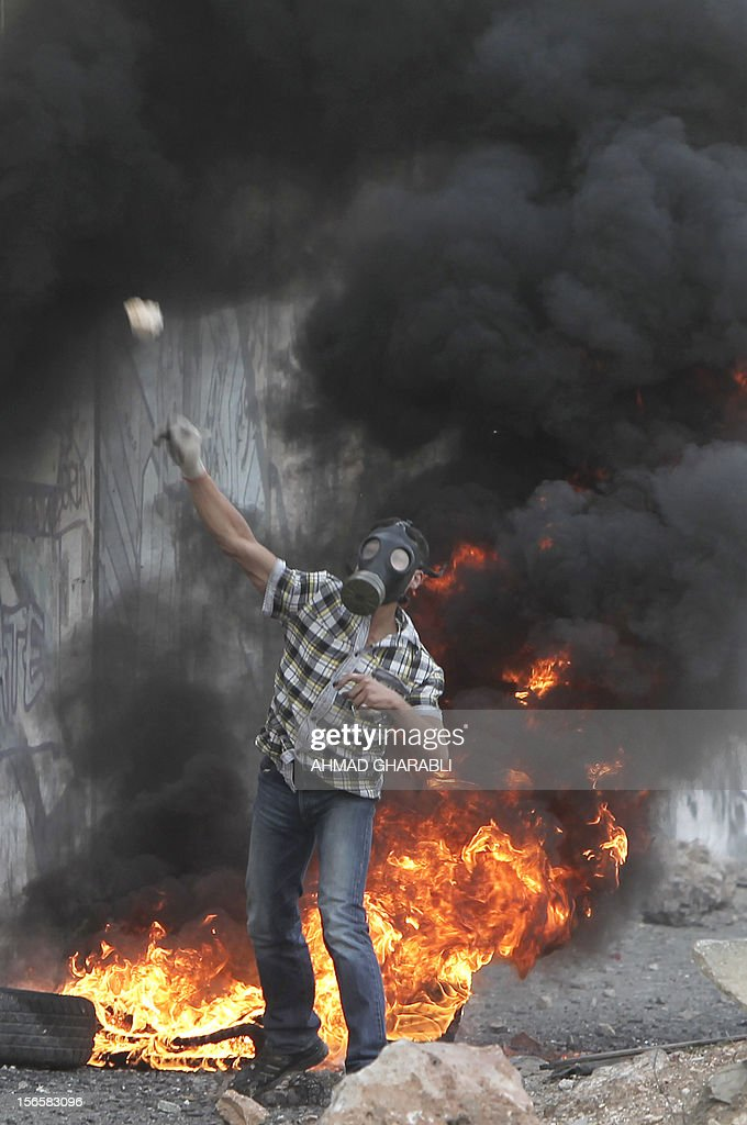 A Palestinian throws a stone during clashes with Israeli soldiers at the Qalandia checkpoint, in the Israeli occupied West Bank, on November 17, 2012 Israeli strikes on Gaza killed 10 Palestinians and destroyed the Hamas government headquarters as Israel called up thousands more reservists for a possible ground war.