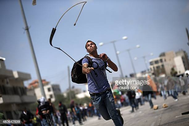 A Palestinian throws a stone towards Israeli police close to the Israeli Ofer military prison in West Bank town of Betunia on April 4 during clashes...