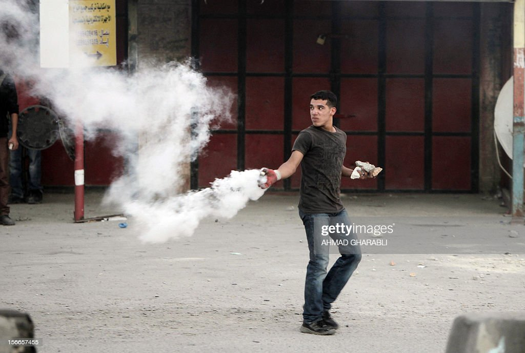 A Palestinian throws back a tear gas canister fired by the Israeli military during a protest against Israel's operations in Gaza the Qalandia checkpoint, in the Israeli occupied West Bank, on November 18, 2012. Israel's Foreign Minister Avigdor Lieberman said that Israel would not negotiate a truce with Gaza Strip's Hamas rulers as long as rocket fire continues from the Palestinian enclave