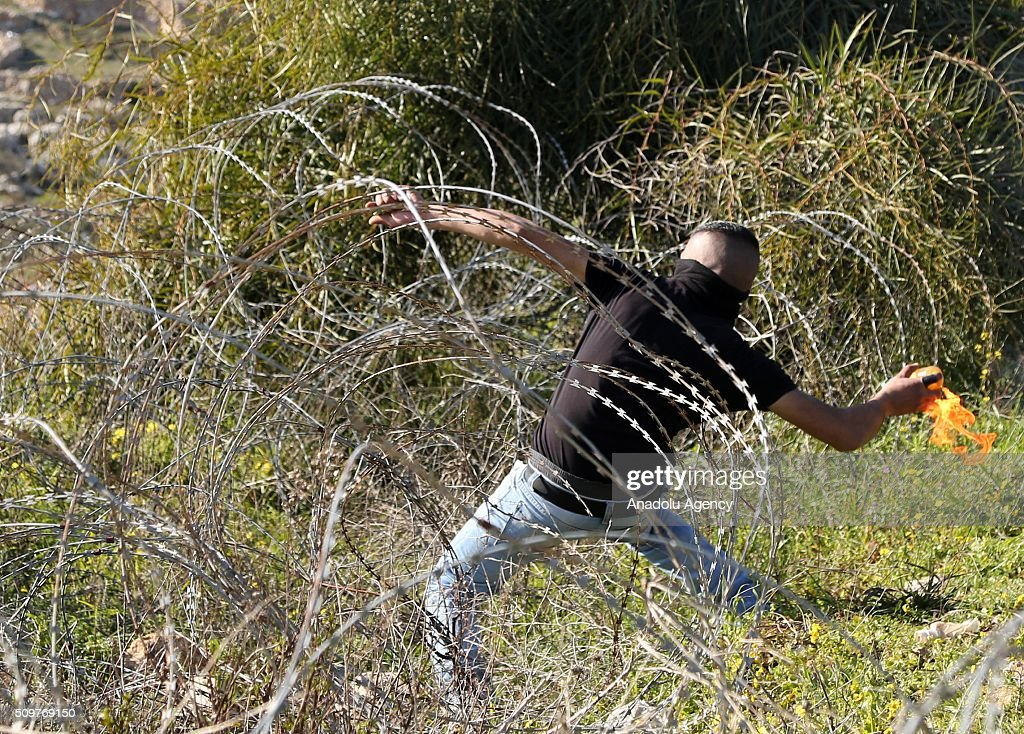 A Palestinian throws stones at Israeli soldiers during a protest against Israel's practices, its settlement policies, its decision on administrative detention and the continuing detention of journalist Mohammed al-Kayak who has been on hunger strike for 80 days against arbitrary measures, in front of Ofer prison in the west of the city of Ramallah on the West Bank on February 12, 2016. Palestinians threw back tear gas capsules used in an intervention by the Israeli security forces.