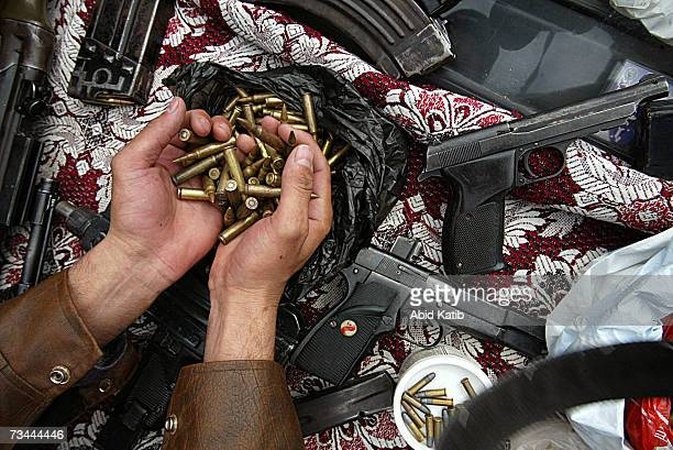 Palestinian trader displays assorted ammunition guns and hand grenades for sale at a local market on February 27 2007 in Gaza city Gaza Strip Some...