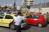 A Palestinian traffic policeman tries to facilitate the traffic for the commuters as taxi drivers park their cars to protest against rising fuel...