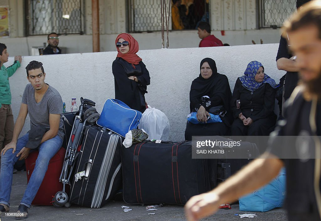 Palestinian travelers wait to cross into Egypt at the Rafah crossing terminal in the southern Gaza Strip on the border with Egypt on October 08, 2013. Hundreds of patients, students and foreign residents from the Palestinian side have rushed to the Rafah crossing after the Egyptian announcement of re-opening it for 5 days.