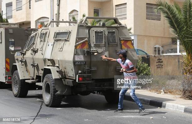 Palestinian tries to open the door of Israeli security forces' armoured vehicle as he holds rocks in his hand after a clash between Israeli security...