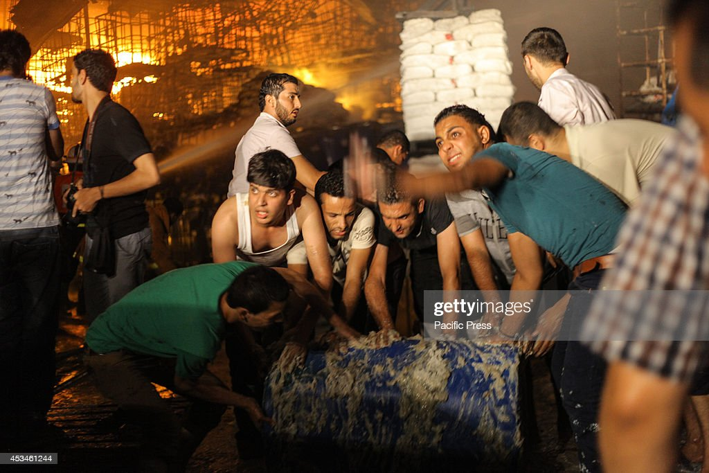 Palestinian trying to help extinguish a fire in a factory for chemicals in the west of Gaza City because of an Israeli air strike, the bombing came after the approval of the Palestinians and Israelis on the Egyptian-brokered truce for 72 hours to stop the fire between the two sides.