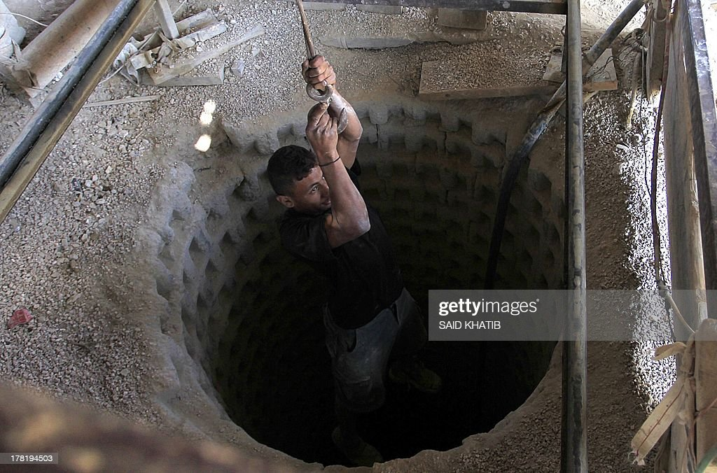 A Palestinian tunnel worker is lowered on a rope into a smuggling tunnel dug beneath the Gaza-Egypt border in the southern Gaza Strip on August 27, 2013. Egyptian security forces have stepped up a crackdown campaign on smuggling tunnels between Egypt and the Gaza Strip since July, Hamas officials said. AFP PHOTO/SAID KHATIB