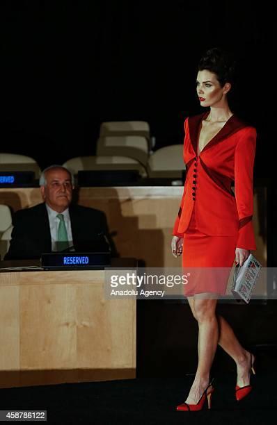 Palestinian UN Ambassador Riyad Mansour looks on as a model displays a creation from Palestinianborn Italian fashion designer Jamal Taslaq's...