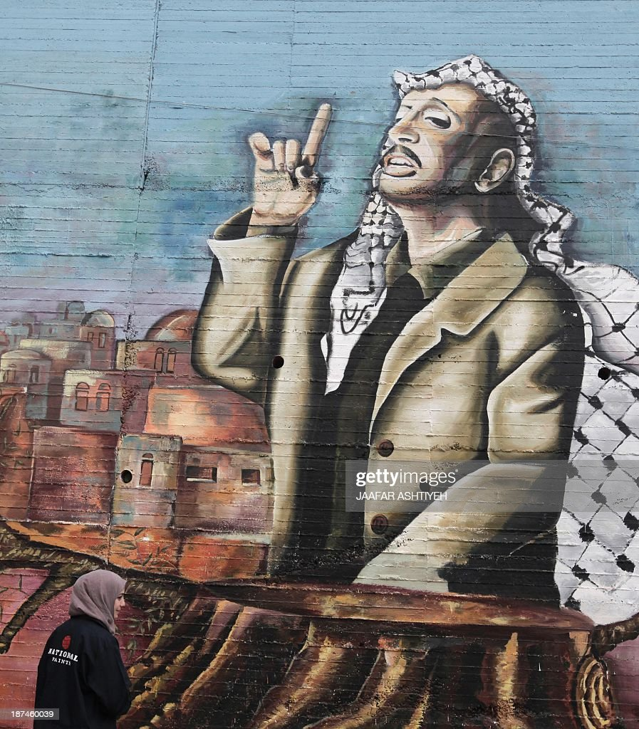 A Palestinian university student stands in front of a huge mural, painted by the students, depicting the late Palestinian leader Yasser Arafat in the West Bank city of Nablus, on November 9, 2013. The Palestinians said on November 8, that Israel is the only suspect in the 'assassination' of Yasser Arafat, a day after Swiss experts said tests suggested their veteran leader was killed by polonium poisoning.