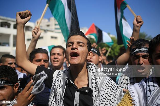 Palestinian university students shout slogans during a rally to express their solidarity with Palestinians clashing with Israeli security forces in...