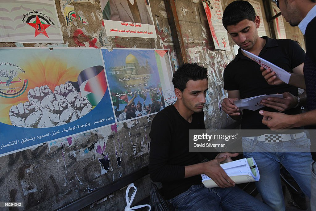 Palestinian university students sit in front of a wall covered with nationalist posters as they wait for their bus at the town's central station on April 6, 2010 in Jenin, West Bank. The Cinema Jenin team of German professionals, local Palestinian staff and foreign volunteers, with funding from the German government, the Roger Waters foundation and other sponsors, are tuning the city's run-down cinema into a modern cinematheque. Their stated aim is to encourage a culture of cinema-going for both the population of Jenin and its refugee camp, and to provide the city with a sustainable cultural centre while fostering principles of peaceful conflict resolution, co-existence and acceptance of others by denouncing all forms of violence and fanaticism.