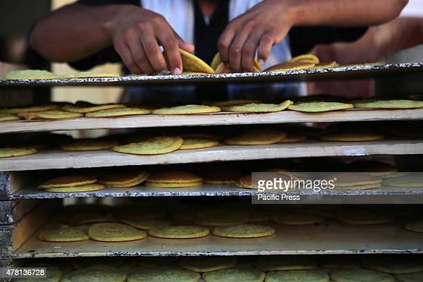 Palestinian vendor prepares traditional pancakes known as ''Qatayef'' in a street market on the fifth day of the holy month of Ramadan in Rafah in...