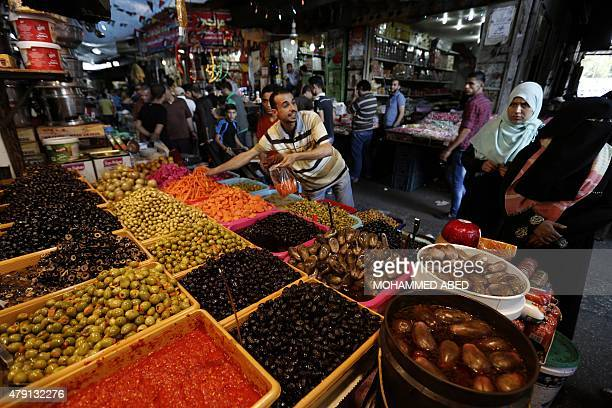 A Palestinian vendor sells olives and vegetables at an old market in Gaza City on the 14th day of the holy fasting month of Ramadan on July 1 2015...