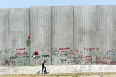 Palestinian walks alongside Israel's security wall July 31 2003 during a protest against the 8meter high barrier that flanks the West Bank...