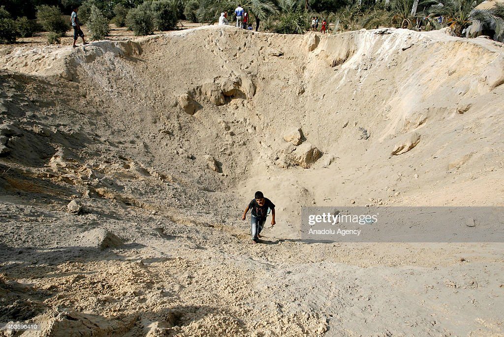 A Palestinian walks inside a crater caused by an Israeli strike, ahead of the announcement of a five-day temporary ceasefire in Khan Younis town of Gaza, on August 14, 2014. A new five-day ceasefire between Palestinian factions and Israel went into effect on Thursday as part of efforts aimed at reaching a permanent truce deal. The Palestinian death toll from Israel's weeks-long military onslaught on the Gaza Strip has risen to 1959, according to a Palestinian Health Ministry spokesman.