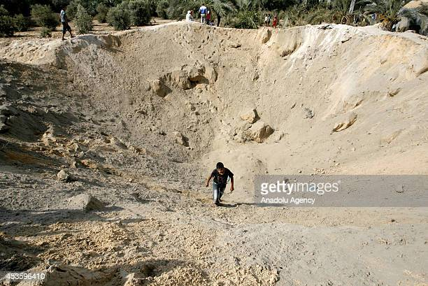 Palestinian walks inside a crater caused by an Israeli strike ahead of the announcement of a fiveday temporary ceasefire in Khan Younis town of Gaza...