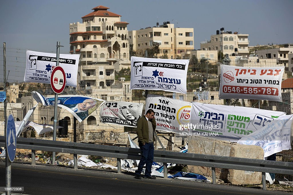 A Palestinian walks past campaign posters for Israeli Prime Minister Benjamin Netanyahu and other candidates near the West Bank village of Hizma on January 16, 2013 ahead of the January 22 general election in Israel.