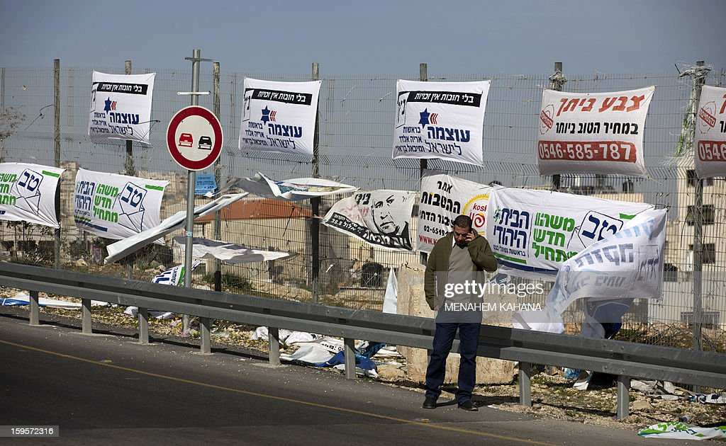 A Palestinian walks past campaign posters for Israeli Prime Minister Benjamin Netanyahu and other candidates near the West Bank village of Hizma on January 16, 2013 ahead of the January 22 general election in Israel. AFP PHOTO / MANAHEM KAHANA