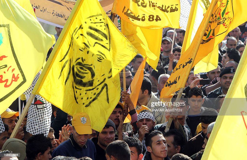 A Palestinian waves a flag bearing the image of late Palestinian leader Yasser Arafat (L) who founded the Fatah movement, alongside other flags as they celebrate the 48th anniversary of the founding of the Gaza branch of the party during a ceremony in the West Bank city of Nablus on January 3, 2013. The anniversary commemorates the first operation against Israel claimed by its armed wing then known as Al-Assifa (The Thunderstorm in Arabic) on January 1, 1965.