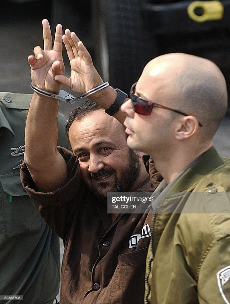 Palestinian West Bank Fatah leader Marwan Barghuti flanked by Israeli guards, flashes the V-sign for victory as he walks into a Tel Aviv court 20 May 2004. An Israeli court was expected to hand down its verdict on a string of terror charges against Barghuti widely seen as the inspiration behind the Palestinian intifada. The 44-year-old member of the Palestinian parliament is charged with 26 counts of murder and heading Al-Aqsa Martyrs Brigades, an armed offshoot of Fatah responsible for a string of deadly anti-Israel attacks.
