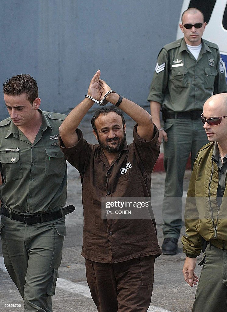 Palestinian West Bank Fatah leader Marwan Barghuti flanked by Israeli guards walks into a Tel Aviv court 20 May 2004. An Israeli court was expected to hand down its verdict on a string of terror charges against Barghuti widely seen as the inspiration behind the Palestinian intifada. The 44-year-old member of the Palestinian parliament is charged with 26 counts of murder and heading Al-Aqsa Martyrs Brigades, an armed offshoot of Fatah responsible for a string of deadly anti-Israel attacks.
