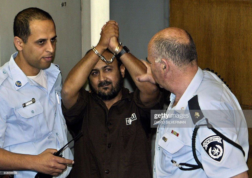 Palestinian West Bank Fatah leader Marwan Barghuti gestures as he arrives in the Tel Aviv district court 20 May 2004. Barghuti, who was found guilty on several counts of murder by the court, will be handed down his sentence on June 6. The 44-year-old member of the Palestinian parliament is charged with 26 counts of murder and heading Al-Aqsa Martyrs Brigades, an armed offshoot of Fatah responsible for a string of deadly anti-Israel attacks. AFP PHOTO/David SILVERMAN