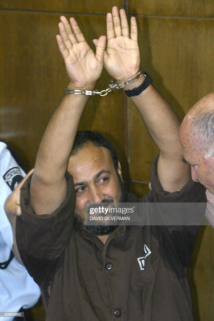 Palestinian West Bank Fatah leader Marwan Barghuti gestures as he is lead by Israseli police into the Tel Aviv district court 20 May 2004. Barghuti, who was found guilty on several counts of murder by the court, will be handed down his sentence on June 6. The 44-year-old member of the Palestinian parliament is charged with 26 counts of murder and heading Al-Aqsa Martyrs Brigades, an armed offshoot of Fatah responsible for a string of deadly anti-Israel attacks. AFP PHOTO/POOL/David SILVERMAN