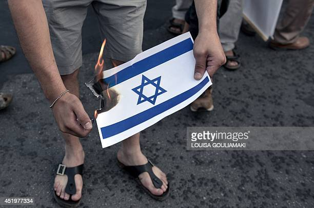 A Palestinian who lives in Greece burns a small Israeli flag on July 10 2014 near the Israeli embassy in Athens during a demonstration by...