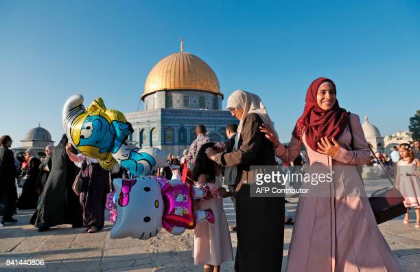 A Palestinian woman adjusts a headband on a girl's head as she carries balloons while celebrating on the first day of Eid alAdha by the Dome of the...