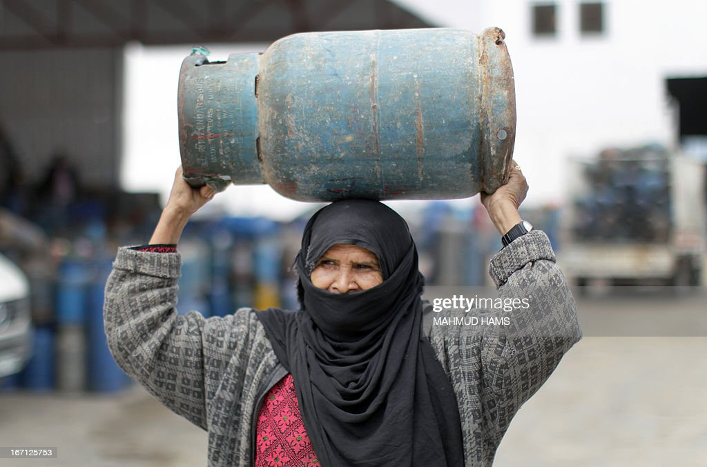 A Palestinian woman carries an empty gas bottle to be refilled at a warehouse in Gaza City on April 21, 2013. The Gaza Strip has been facing a gas crisis for the past two months partially due to the frequent closure of their border crossings by neighboring Israel.