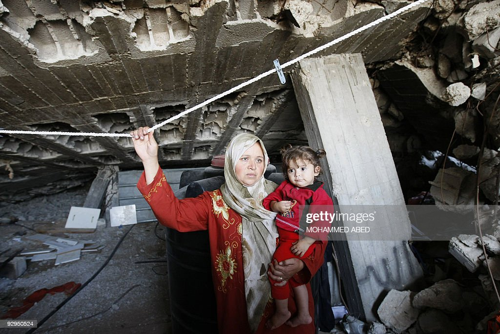 A Palestinian woman carries her child as she stands amid the ruins of a house during a visit by Maxwell Gaylard the UN humanitarian coordinator for...