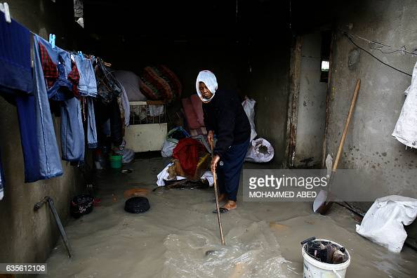 Palestinian woman cleans her home at a flooded area following heavy rainfall in the Jabalia refugee camp in the northern Gaza Strip on Fbruary 16...