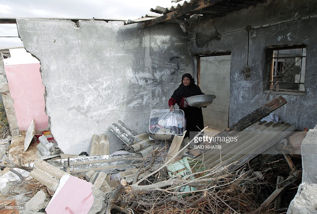 A Palestinian woman collects items from her destroyed home following an Israeli military air strike in Rafah town in the southern Gaza Strip, on November 11, 2012. The flare-up which began November 10, was one of the most serious since Israel's devastating 22-day operation in the Gaza Strip over New Year 2009, has culminated in six Palestinians being killed and 32 injured by Israeli strikes after militants fired on an Israeli jeep, wounding four soldiers, medics and witnesses said.