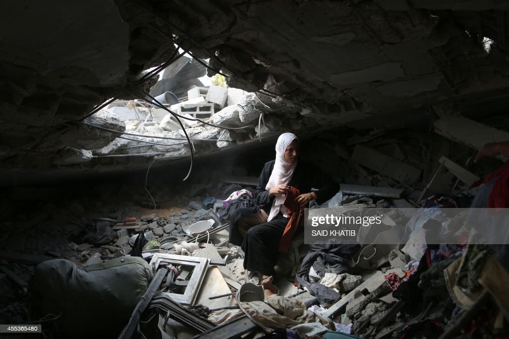 A Palestinian woman collects items from the rubble of her house which was destroyed by Israeli strikes during the summer's fierce offensive on the...
